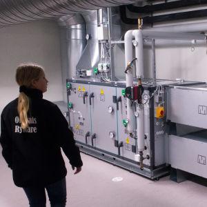 En flicka tittar på ventilationsaggregat
