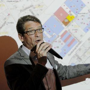 Tapani Mäkinen talar i mikrofon och pekar mot en tavla i bakgrunden.