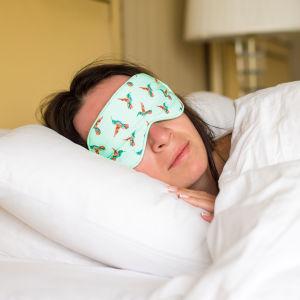 Kvinna ligger under täcket med en sovmask över ögonen.