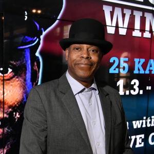 Michael Winslow poserar framför en stor affisch med hand ansikte.
