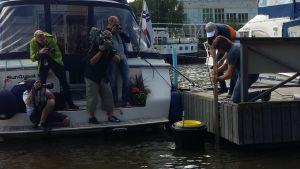 Flera fotografer följer med då Pete Ceglinski sätter fast havssoptunnan vid en brygga i Åbo gästhamn.