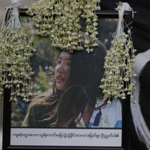 En bild på Mya Thwe Thwe Khaing används under en demonstration i Myanmar. Bredvid en stiliserad bild av en hand med tre uppsträckta fingrar.