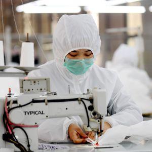 Efterfrågan på skyddsutrustning är enorm i Kina just nu. På en fabrik i Ningjin, söder om Peking, bar arbetarna själva skyddsdräkter medan de tillverkade dem.