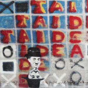 Graffititeos, jossa lukee teksti taide sekä piirrokset Charlie Chaplinin Kulkuri-hahmosta sekä Anonymous-hahmosta Taidekeskus Antareksessa Sippolassa.