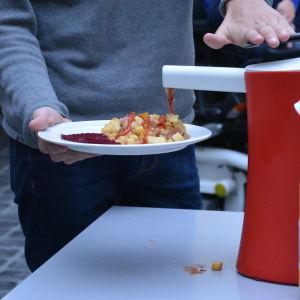 En person klämmer ketchup på sin pyttipanna i en skolmatsal.