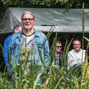 Publik står och lyssnar, i bakgrunden ett terasstält, i förgrunden växer högt gräs.