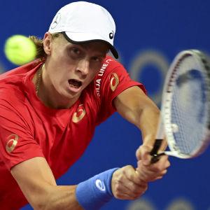 Emil Ruusuvuori böjer sig för att träffa en tennisboll.