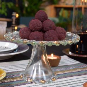 Ett bord som är dukat med ett kakfat med lila aroniabollar.