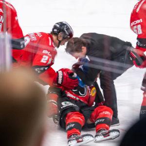 En liggande Otto Kivenmäki får vård på isen.