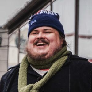Iso mies mustassa takissa, vihreässä kaulaliinassa ja sinisessä pipossa seisoo talvisella kadulla ja nauraa.