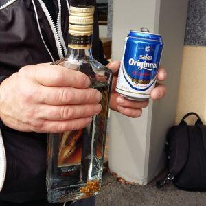 En man håller en vodkaflaska i ena handen och en ölburk i den andra.