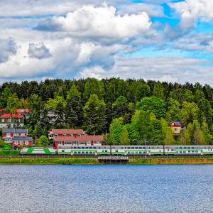 Kuva suomalaisessa maisemassa kulkevasta junasta. Metsää takana, vettä edessä.