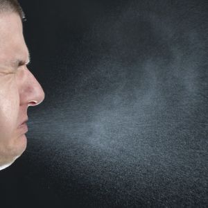 En man nyser och det sprutar ut partiklar ur hans mun.