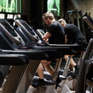 Två män sitter på konditionscyklar i ett tomt gym.