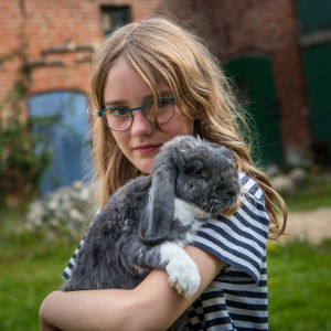Tyttö pitää kania sylissä.