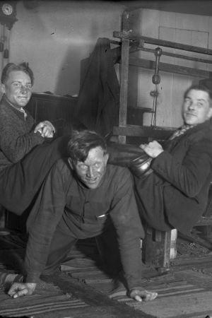 """Tre män leker """"lyfta saltsäck"""", där en person är på golvet på alla fyra, och två andra är på den förstas rygg medan han försöker stiga upp. Bilden är tagen 1935 i Bromarf."""