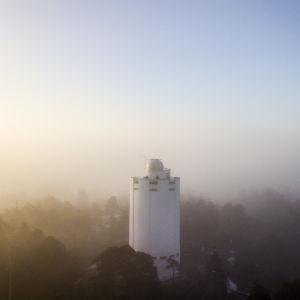 Karis vattentorn sett ur luften. Dis och sol, tidig marsmorgon. Gör himlen svagt rosa, orange, lila och blå.