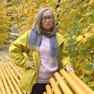 Leena Stolzmann har på sig en gul jacka och står omgiven av gula höstlöv. Hon ser allvarlig ut.