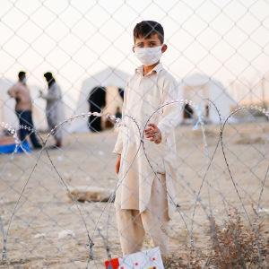 En liten pojke i munskydd tittar in i kameran genom stängsel på gränsen mellan Afghanistan och Iran. I bakgrunden syns tält och två män som pratar med varandra.