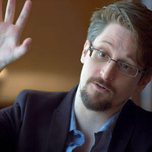 Edward Snowden med ena handen uppsträckt  i ett hotellrum i Moskva  / April 2019, Moskva