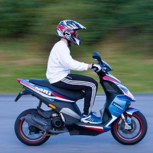 Pojke kör fort med moped