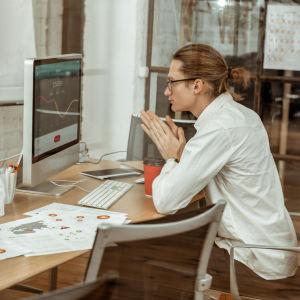 En person sitter vid en dator och jobbar.