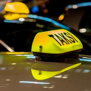 Keltainen taksikyltti taksin katolla.