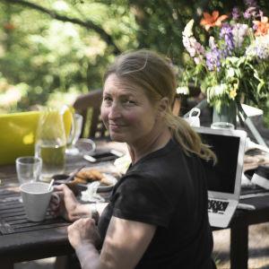 En kvinna och man sitter vid ett trädgårdsborg utomhus. Vädret är soligt. I bakgrunden syns en hund. Bägge ser mot kameran.