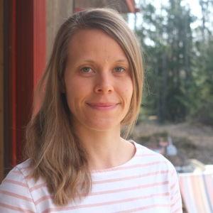 Blond kvinna ute på terass i vårsol.