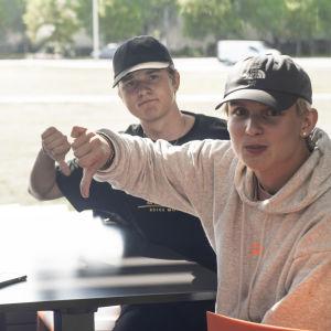 Fyra killar sitter vid ett bord. De ser in i kameran och visar tummen ned.