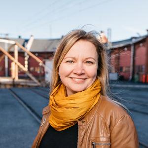 Marie Söderman står ute på gården vid lokstallet i Åbo.