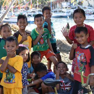 Indonesiska barn poserar för kameran. Många av dem visar olika tecken med fingrarna.