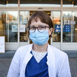 Kvinna i läkarrock och munskydd står framför sjukhusingång och tittar in i kameran.