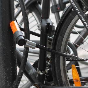 Närbild på en cykel som låsts fast i en ställning.