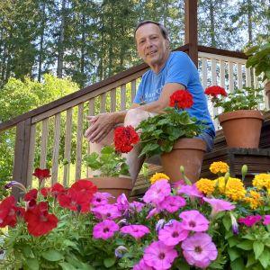 En medelålders man i shorts och t-skjorta sitter på en trappa. Bilden är tagen från sidan och nerifrån så att blommorna på trappan syns i förgrunden.