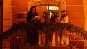 En medelålders kvinna samt en ung lucia och två tärnor står på en trappa utomhus. Kvinnan läser från ett papper och luciaföljet lyssnar.