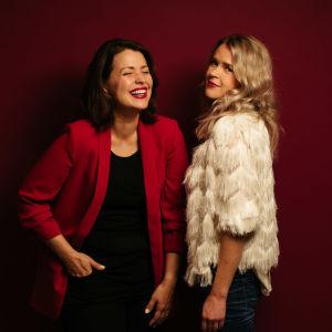 Två kvinnor poserar framför fondvägg