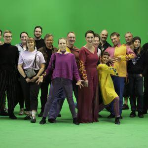 21 Mirages-elokuvan tekoon osallistunutta ihmistä seisoo ryhmässä vihreää kangastaustaa vasten.