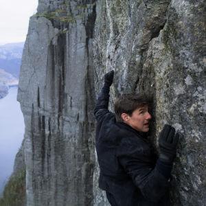 Ethan Hunt (Tom Cruise) klänger sig fast på en hög klippvägg.