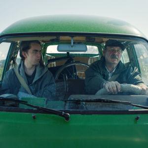 Stefan (Martin Paul) och Nisse (Peik Stenberg) sitter tillsammans i en grön paketbil.