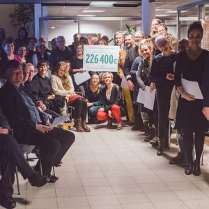 Många människor inne i en banklokal. En stor låtsascheck med summan  226 400 euro visas upp.