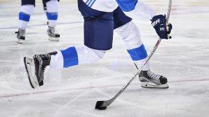 Ishockeyspelare skjuter puck.