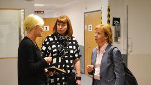 Två kvinnor står i en sjukhuskorridor och lyssnar på en tredje som pratar.