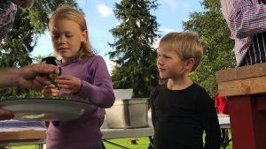 Emelie och Arvid Munsterhjelm står i ett provisoriskt utomhuskök med Matias Jungar och Michael Björklund.