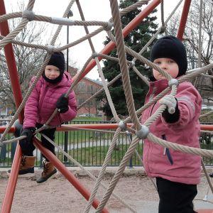Astrid och Ebba Tuominen, två flickor i rosa jackor och svarta mössor, leker i en klätterställning med metallvajrar.