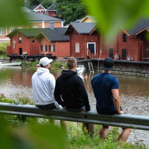 De tre pojkarna sitter med ryggen mot och tiitar ut över Borgå å och strandbodarna.