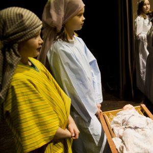 Två lågstadiebarn med dukar runt huvudet står framför en krubba på en scen, en grupp lågstadiebarn utklädda till tärnor står framför scenen.