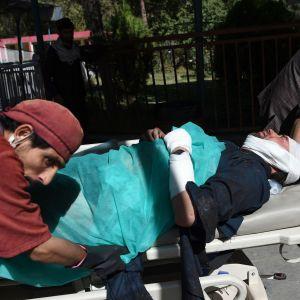 Två personer drar en person på en bår.