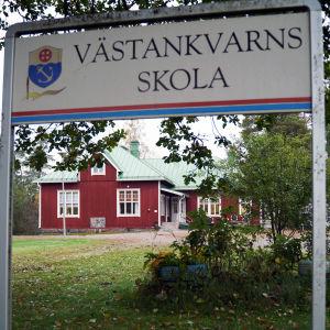 En röd, äldre byskola skymtar bakom en skylt där det står Västankvarns skola.
