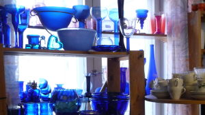 Blå glasföremål på några hyllor. Loppissaker.
